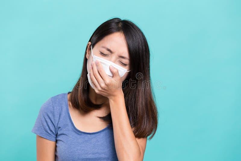 Vrouw die gezichtsmasker en hoest dragen stock afbeeldingen
