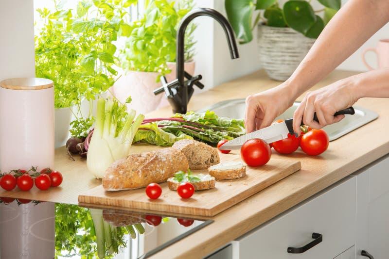 Vrouw die gezond ontbijt voorbereiden, snijdend een tomaat in halve en organische kruiden en groenten in een zonnig keukenbinnenl stock fotografie