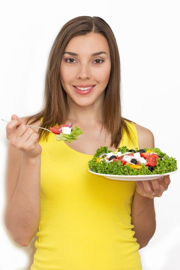 Vrouw die gezond voedsel, Griekse salade eet stock fotografie