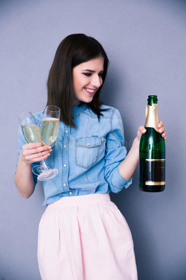 Vrouw die glas twee en fles champagne houden royalty-vrije stock fotografie