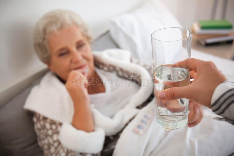 Vrouw die glas water geven aan hogere dame die geneeskunde thuis neemt royalty-vrije stock foto