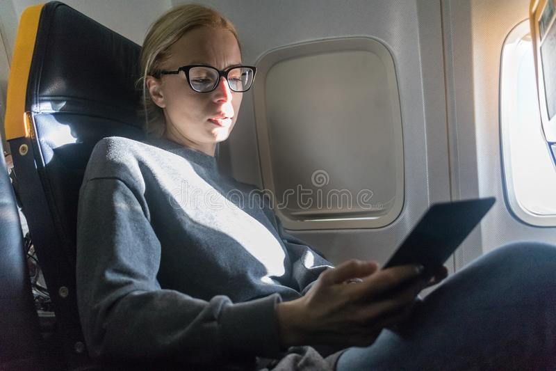Vrouw die glazen dragen die op digitale e-lezer lezen terwijl het reizen door vliegtuig stock afbeeldingen