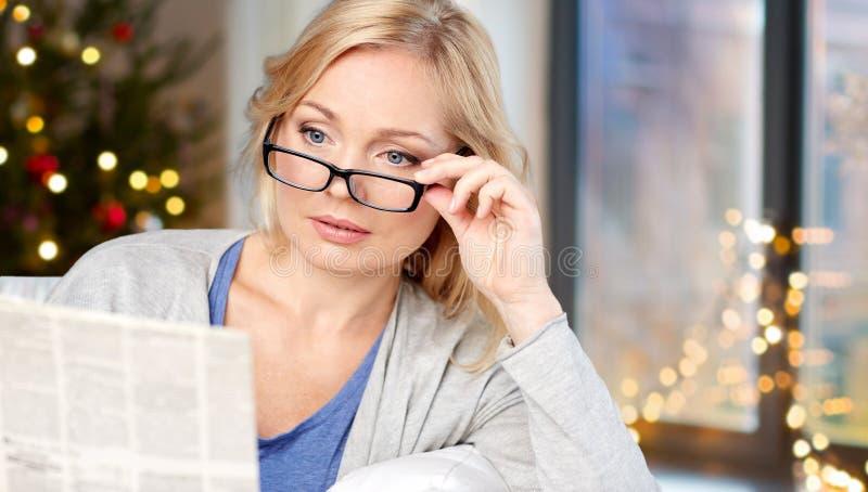Vrouw die in glazen krant over Kerstmis lezen stock foto's