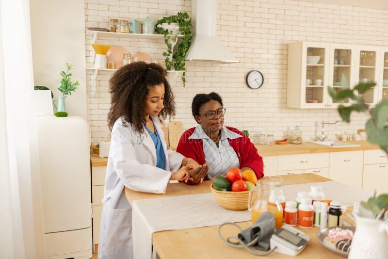 Vrouw die in glazen rust zitten terwijl verpleegster die impuls meten royalty-vrije stock foto