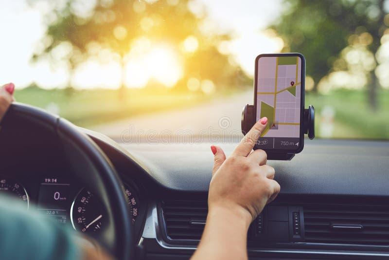 Vrouw die GPS-navigatie in mobiele telefoon gebruikt terwijl het drijven van auto bij zonsondergang royalty-vrije stock afbeelding