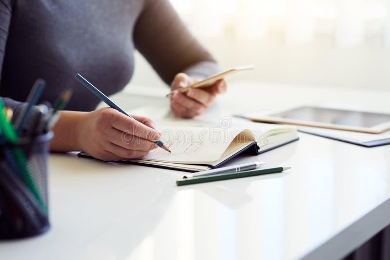 Vrouw die grafisch ontwerp in zijn agenda schetsen stock afbeeldingen