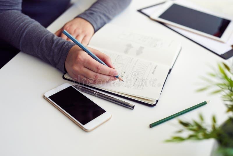 Vrouw die grafische schets in bureau schetsen stock foto