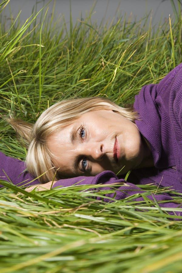 Vrouw die in gras ligt stock foto's