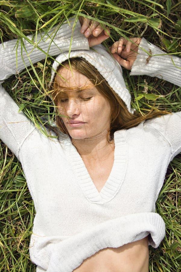 Vrouw die in gras ligt. royalty-vrije stock foto's