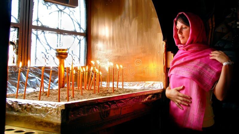 Vrouw die in Griekse kerk het branden van kaarsen bekijken royalty-vrije stock fotografie