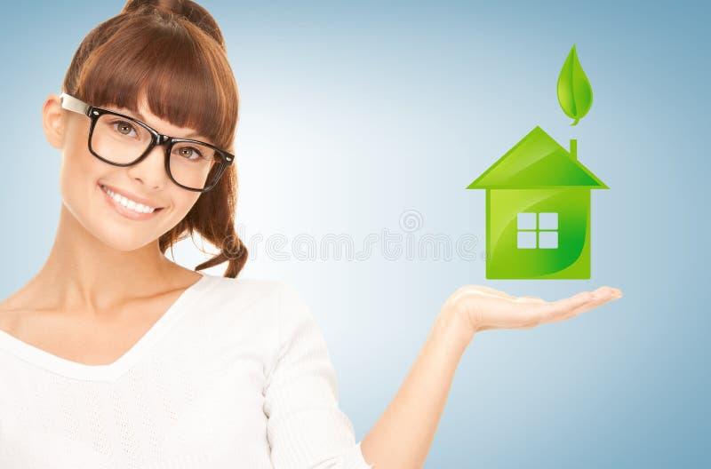 Vrouw die groen huis in haar handen houden royalty-vrije stock afbeeldingen