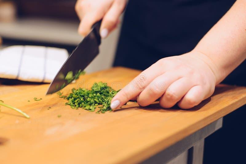Vrouw die groen korianderkruid snijden royalty-vrije stock fotografie
