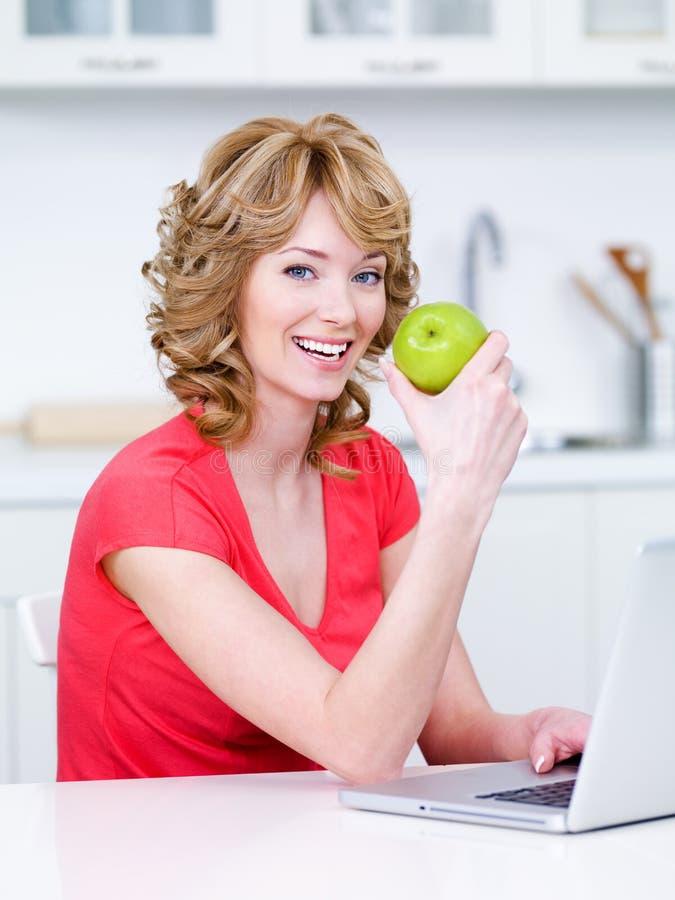 Vrouw die groene appel in de keuken eet stock afbeelding