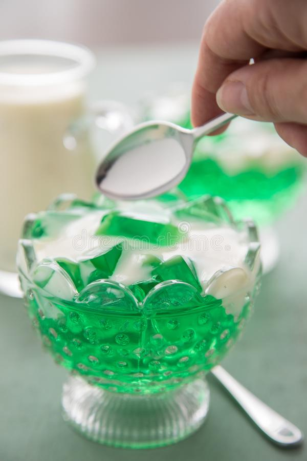 Vrouw die groene bedstrogelei en vanillevla met lepel eten stock afbeeldingen