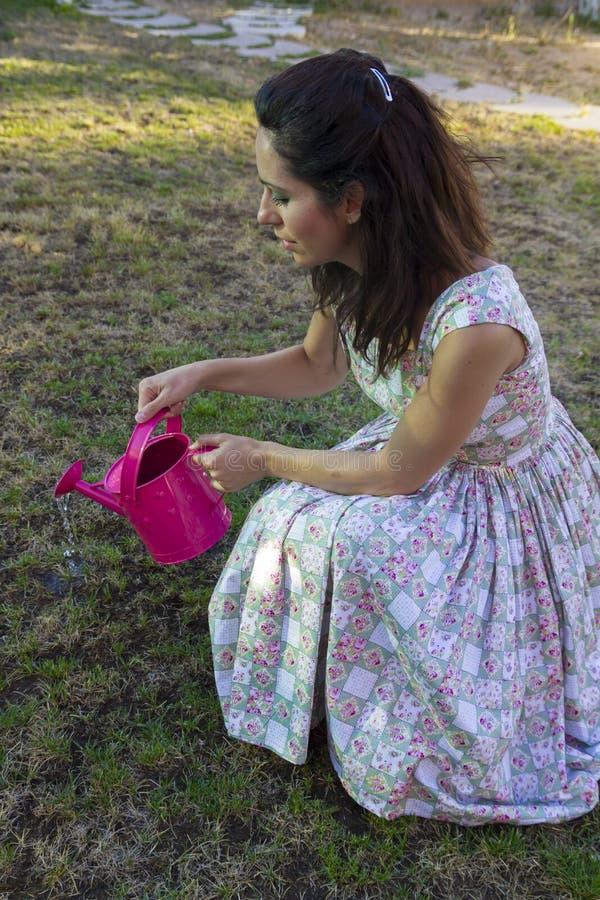 Vrouw die groene tuin water geven.   stock fotografie