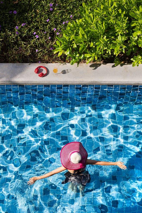 Vrouw die grote hoed dragen die in pool lopen royalty-vrije stock foto's