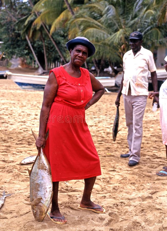 Vrouw die grote vissen op het strand houden stock foto