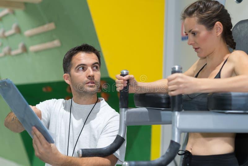Vrouw die in gymnastiek met hulp door persoonlijke trainer uitoefenen stock afbeelding