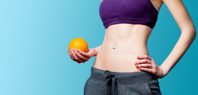 Vrouw die haar abs met sinaasappel na gewichtsverlies tonen stock afbeeldingen