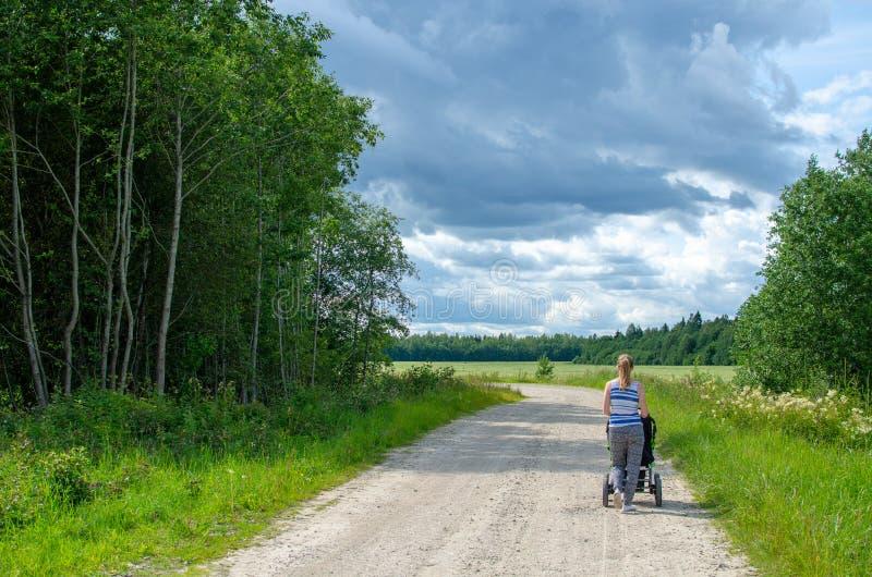 Vrouw die haar baby op een plattelandsweg lopen in de zomer stock foto