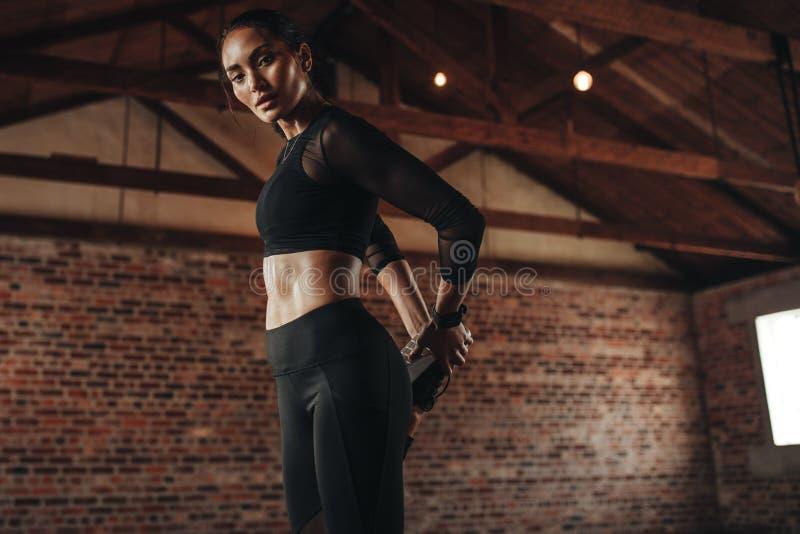 Vrouw die haar beenspieren ontspannen bij gymnastiek stock afbeelding