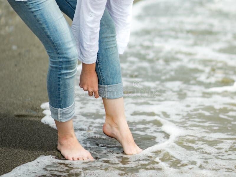 Vrouw die haar broek op het strand rollen royalty-vrije stock afbeelding