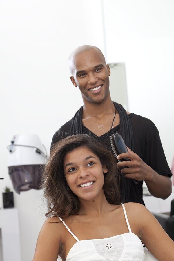 Vrouw die haar die haar krijgen bij schoonheidssalon wordt gestileerd royalty-vrije stock foto