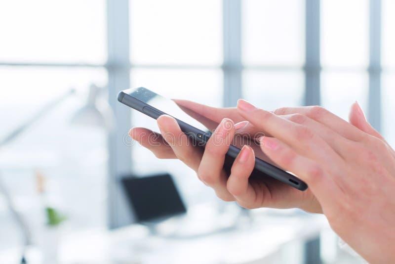 Vrouw die haar digitaal apparaat met behulp van, lezend nieuws, verzendend sms, surfend Internet, die en apps in bureau, close-up stock afbeelding