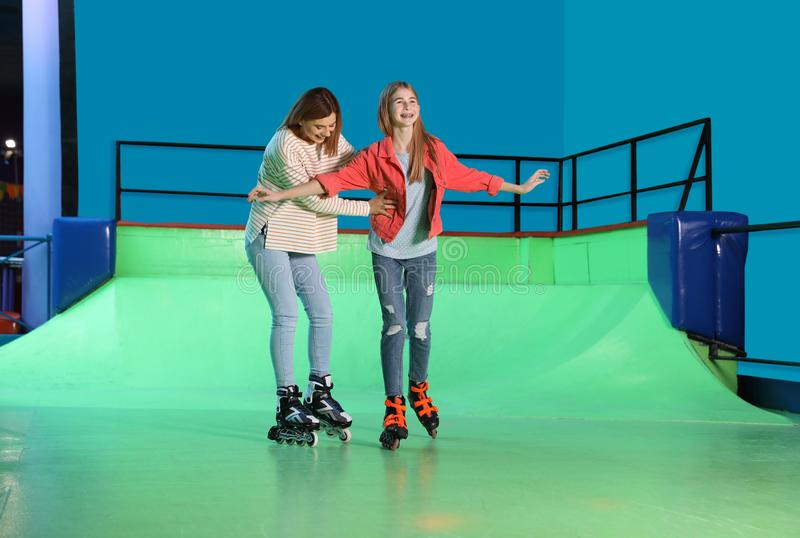 Vrouw die haar dochter onderwijzen bij rolpiste stock afbeelding