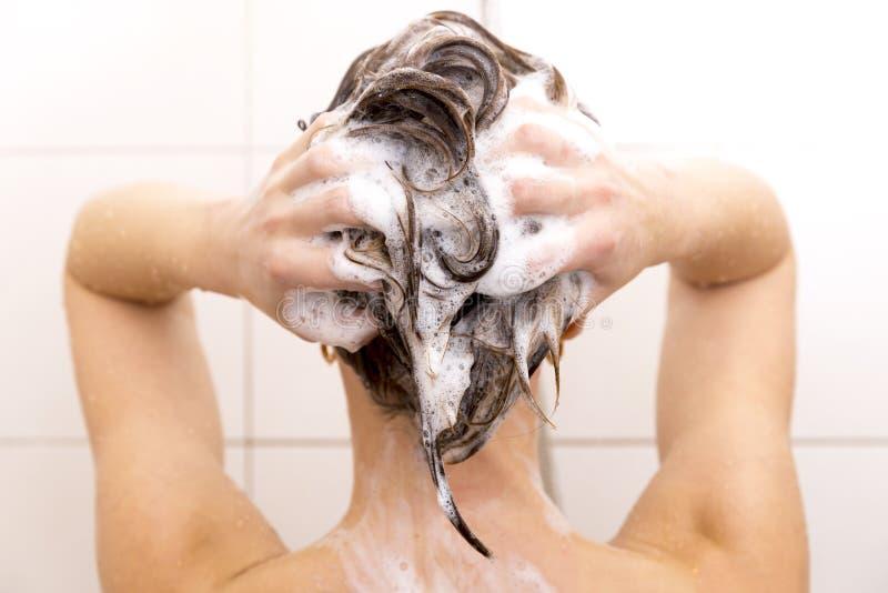 Vrouw die haar haar in douche wassen stock afbeeldingen
