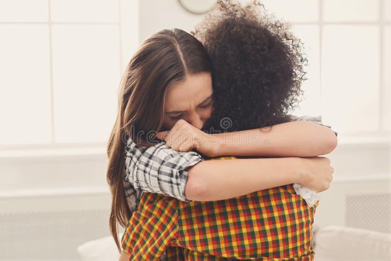Vrouw die haar gedeprimeerde vriend thuis koesteren stock fotografie