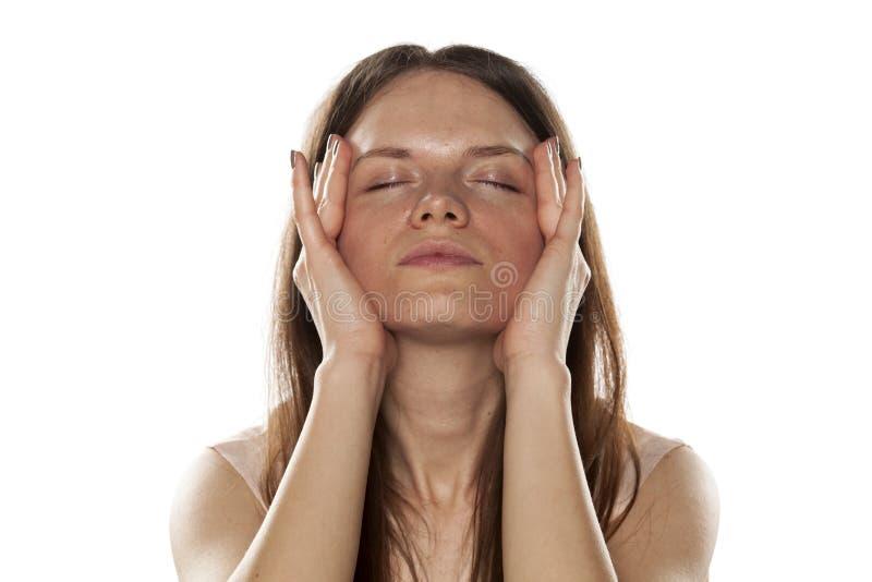 Vrouw die haar gezicht aanhalen stock afbeelding
