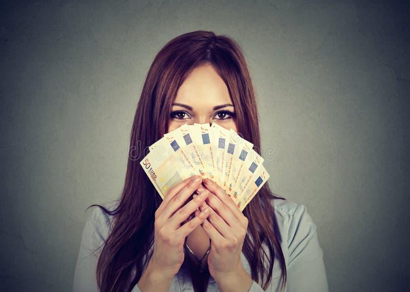 Vrouw die haar gezicht achter euro geldventilator verbergen royalty-vrije stock foto's