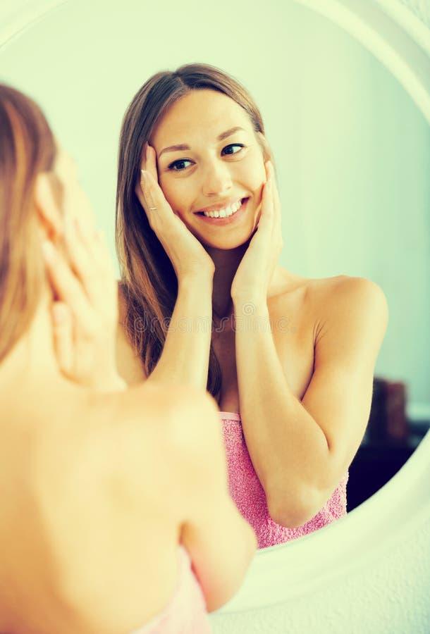Vrouw die haar gezicht onderzoeken door het in spiegel te bekijken stock afbeeldingen