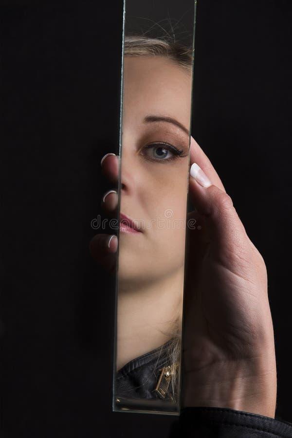 Vrouw die haar gezicht in scherf van gebroken spiegel bekijken royalty-vrije stock foto's