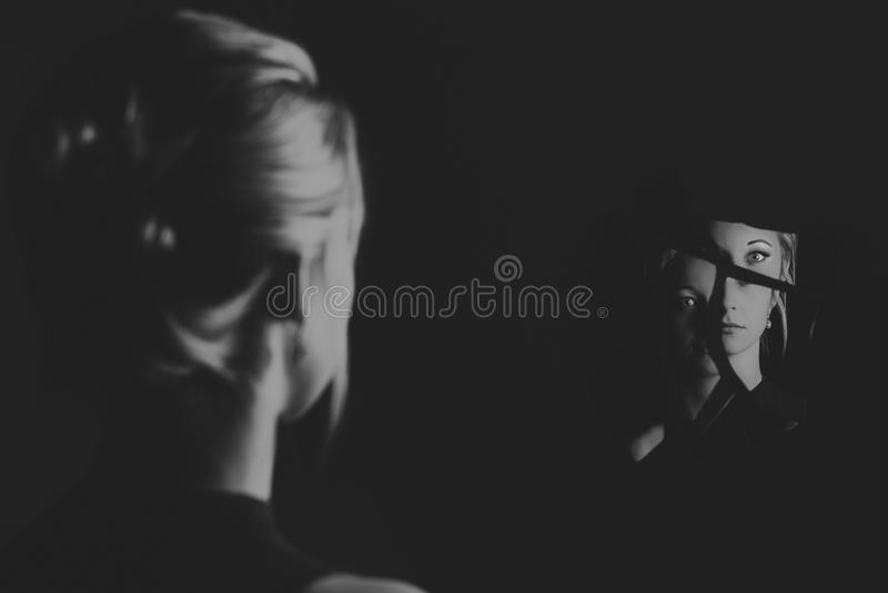 Vrouw die haar gezicht in scherven van gebroken spiegel artistieke mede bekijken royalty-vrije stock foto's