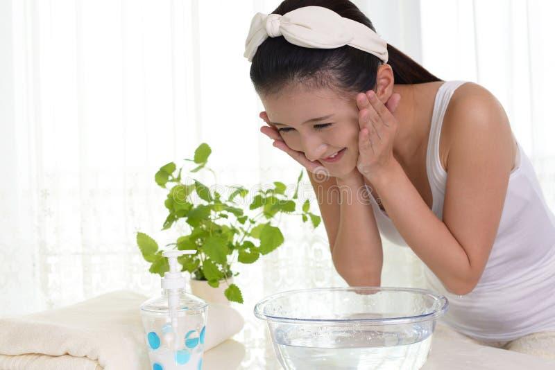 Vrouw die haar gezicht wassen royalty-vrije stock foto's