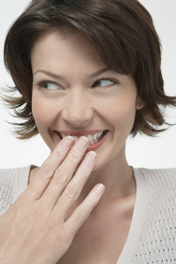 Vrouw die Haar Glimlach verbergen stock foto