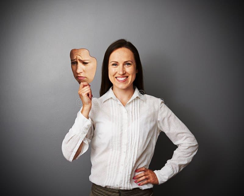 Vrouw die haar goede stemming verbergen onder droevig masker stock foto's