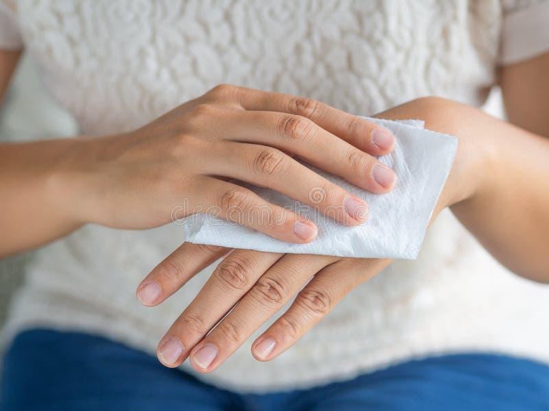 Vrouw die haar handen met een weefsel schoonmaken Gezondheidszorg en medisch c stock fotografie