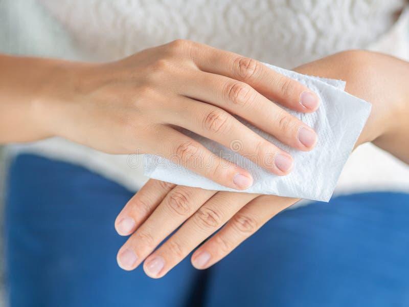 Vrouw die haar handen met een weefsel schoonmaken Gezondheidszorg en medisch c stock afbeelding