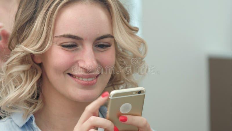 Vrouw die haar het stileren in salon hebben terwijl het doorbladeren van Internet op haar mobiele telefoon, het glimlachen stock afbeelding