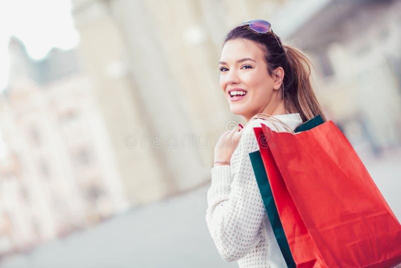Vrouw die haar het winkelen zakken in haar hand houden stock afbeeldingen