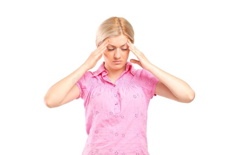 Vrouw die haar hoofd in pijn houdt stock foto
