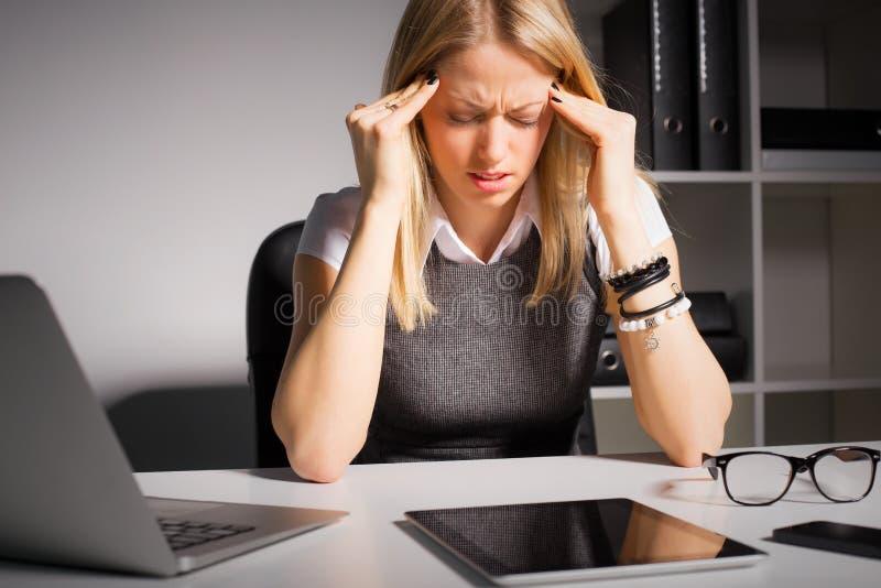 Vrouw die haar hoofd in pijn houdt stock afbeelding