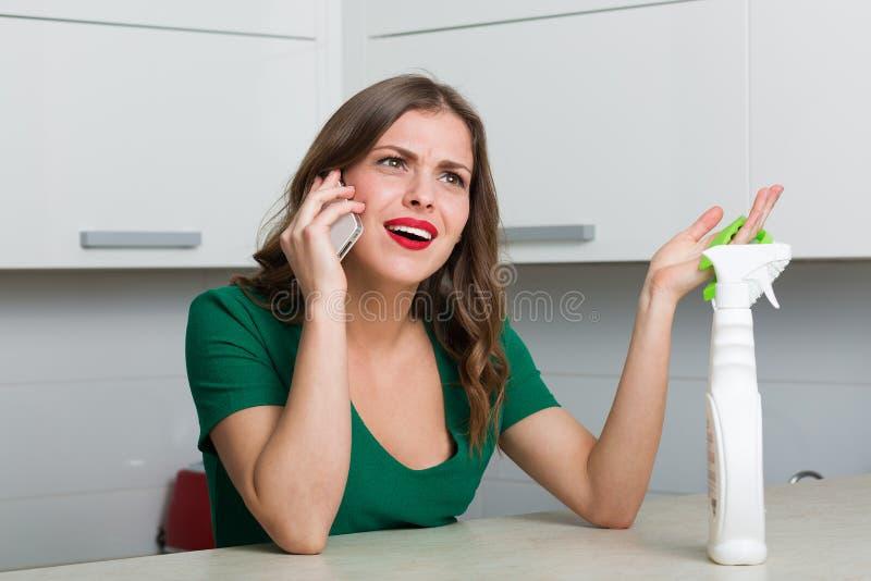 Vrouw die haar keuken schoonmaken stock afbeelding