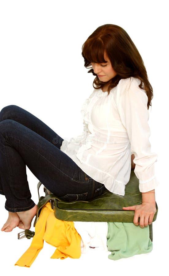Vrouw die haar koffer probeert te sluiten stock fotografie