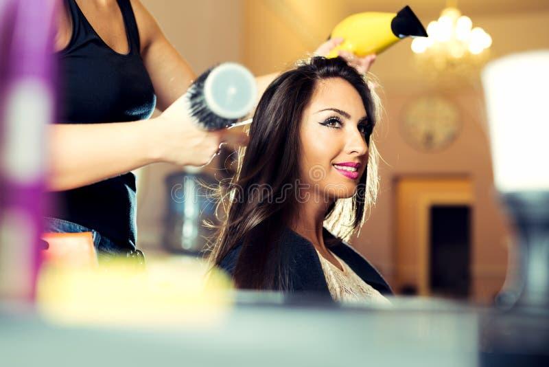 Vrouw die haar haar krijgen bij de haarsalon droog stock afbeelding