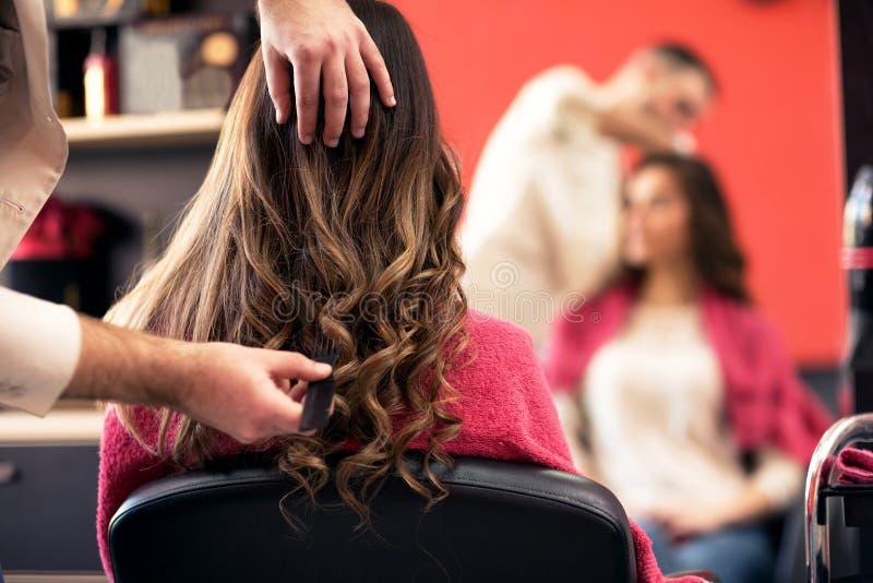 Vrouw die haar die haar krijgen in de salon wordt gedaan stock fotografie