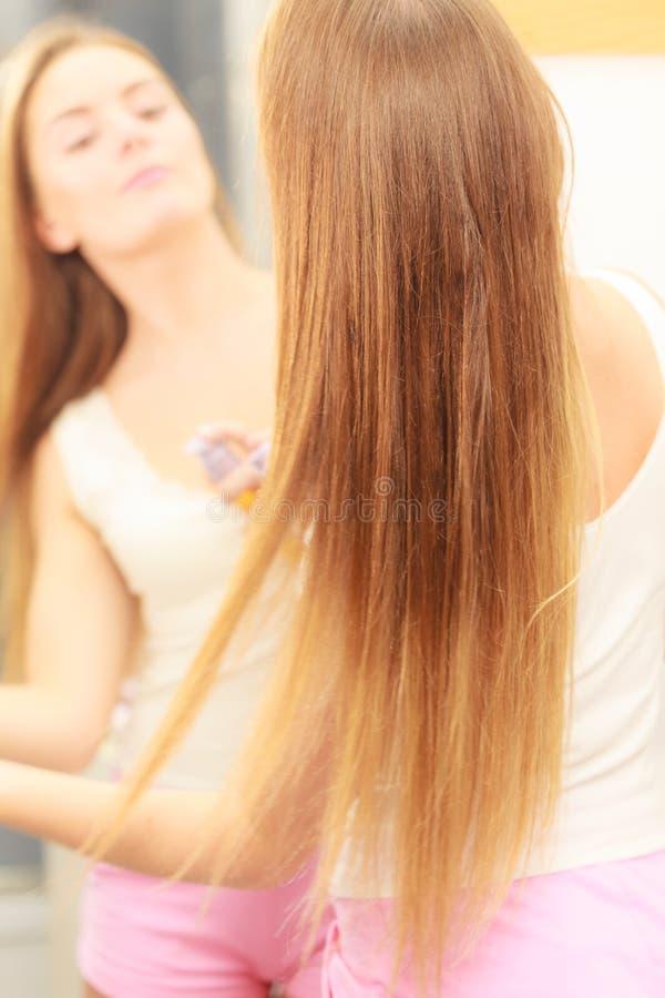 Vrouw die haar lang haar behandelen die kosmetische olie toepassen stock afbeeldingen